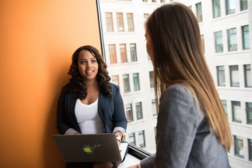 woman standing infront of woman holding laptop